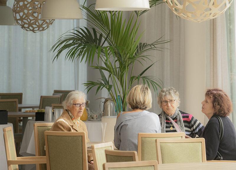 Seniors qui parlent autour d'une table