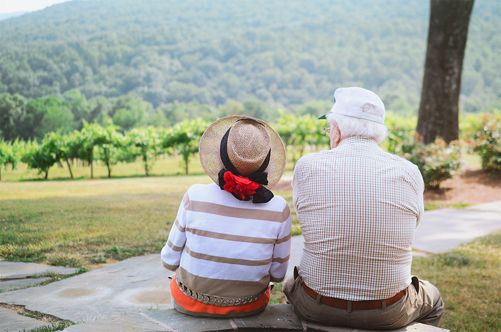 Seniors assis face à un champ de vignes, canicule
